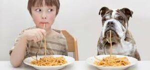 child-and-dog-eating-spaghetti-from-dish