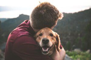man comforting his dog
